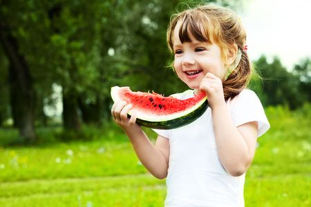 cute little girl eating  watermelon on the grass in summertime photo