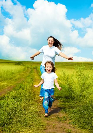 young mother and her little daughter running along the road outdoors on a summer day photo