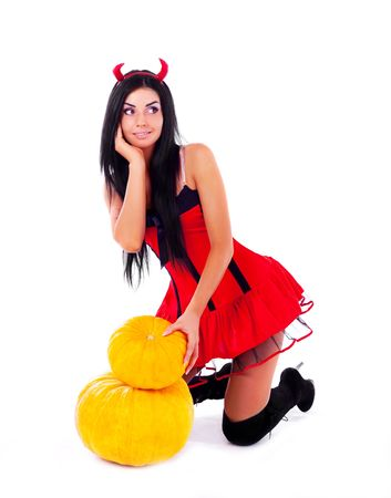 sexy young brunette woman dressed as an imp with a pumpkin photo