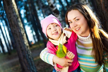 young beautiful mother and her little daughter in the autumn park   photo
