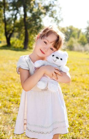 cute happy little girl with a toy in the autumn park on  a warm sunny day photo