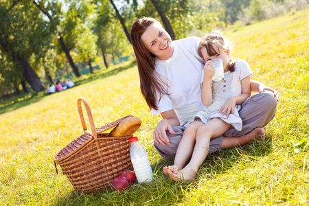 beautiful young mother and her daughter having picnic in the park on a sunny autumn day photo