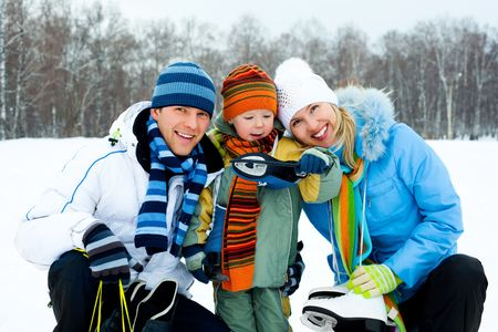 figure skating: happy young parents going ice skating with their son