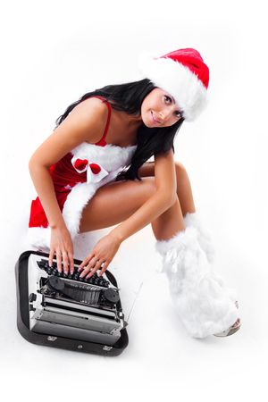 beautiful young brunette woman dressed as Santa printin on the typewriter photo