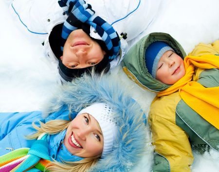 young parents and their son wearing warm winter clothes lie on the snow (focus on the mother) photo