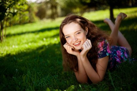 pretty teenage girl on the grass in the park photo