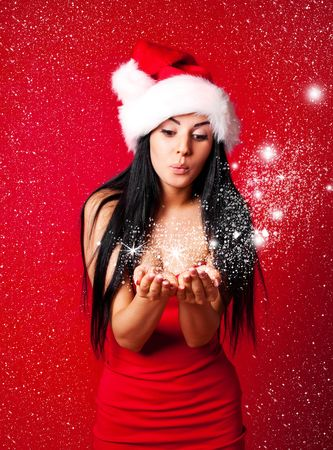 pretty young brunette woman dressed as Santa blowing on the snow on her hands photo