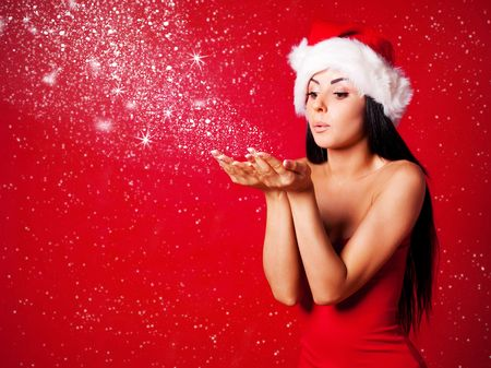 sexy santa girl: pretty young brunette woman dressed as Santa blowing on the snow on her hands Stock Photo
