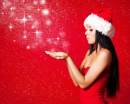 christmas costume: pretty young brunette woman dressed as Santa blowing on the snow on her hands Stock Photo