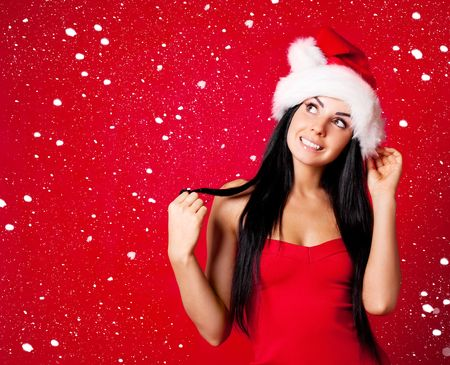 beautiful happy young woman dressed as santa with snow falling on her photo