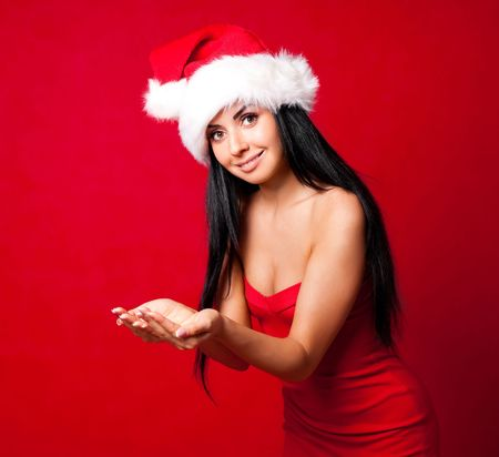 beautiful brunette girl wearing a Santas hat and holding something in her hands, place your product here photo