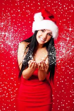 pretty young brunette woman dressed as Santa with snow and start flying out of her hands photo