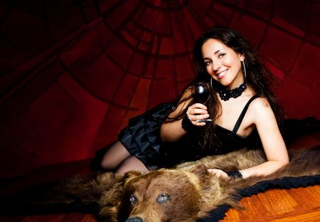 luxurious young brunette woman drinking vine on the bear skin rug Stock Photo - 8191814