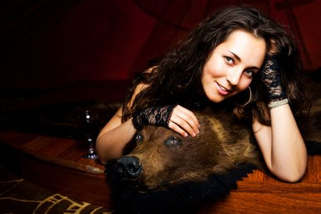 luxurious young brunette woman drinking vine on the bear skin rug Stock Photo - 8191127