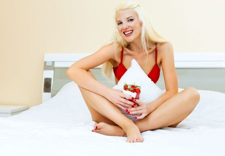 portrait of a sexy young blond woman eating strawberries with cream in her bed at home photo