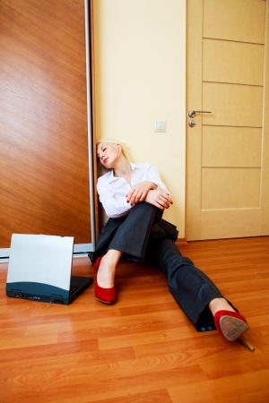 tired young businesswoman sleeping on the floor in the office photo