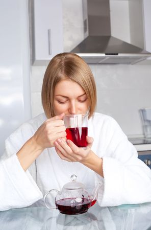 young woman drinking tea at home in the morning in the kitchen photo