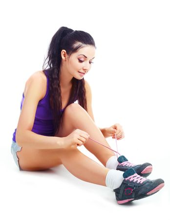 sneakers: pretty brunette girl wearing sports clothes tying shoelaces