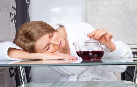 red bathrobe: beautiful sleepy young woman drinking tea at home in the morning