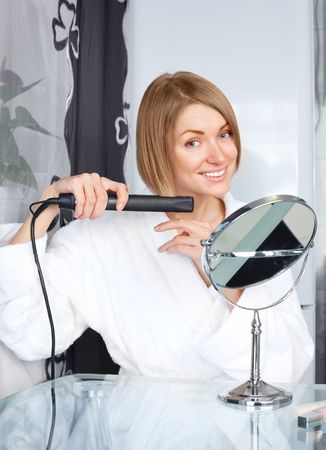 straightener: beautiful young woman using a hair straightener at home Stock Photo