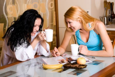 two young beautiful women drink tea in the kitchen and  read a magazine photo