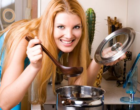 beautiful young blond woman cooking dinner in the kitchen photo