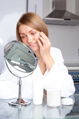 beautiful young woman applying cream on her face at home Stock Photo - 8191810