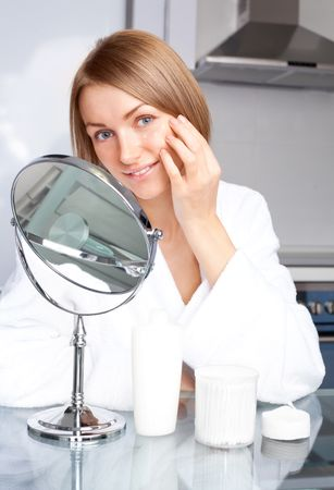 beautiful young woman applying cream on her face at home Stock Photo - 8191788