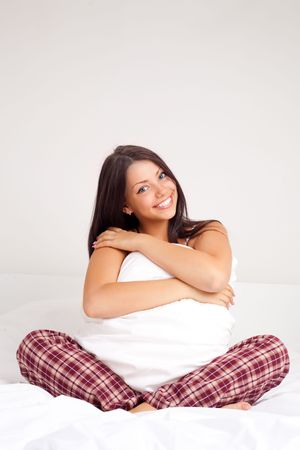 pretty girl sitting on the bed at home and holding a pillow Stock Photo - 8191545