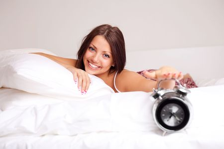 pretty happy girl waking up in the morning and switching off the alarm clock   Stock Photo - 8191458