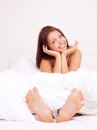 pretty brunette girl sitting on the bed under the blanket photo