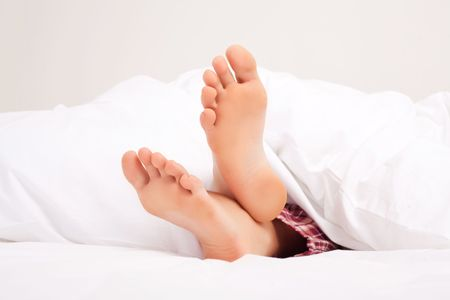 insides: feet of a woman sleeping on the white linen at home Stock Photo