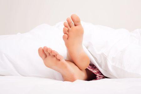 white linen: pies de una mujer durmiendo en el lino blanco en casa