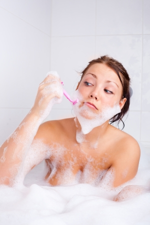 beard woman: humorous picture of a young brunette woman taking a bath and shaving beard Stock Photo
