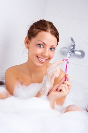 beautiful young brunette woman taking a relaxing bath with foam and using a razor photo