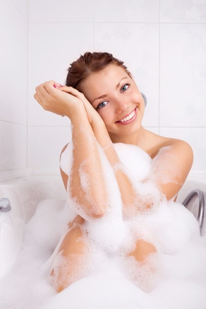 bathtubs: beautiful young brunette woman taking a relaxing bath with foam Stock Photo