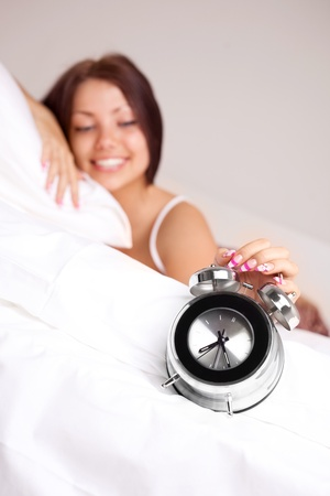 pretty happy girl waking up in the morning and switching off the alarm clock (focus on the clock)  photo
