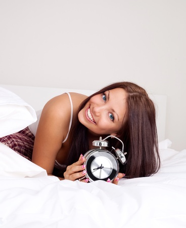 pretty happy girl waking up in the morning and switching off the alarm clock   photo