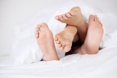 human toe: feet of a couple under the blanket