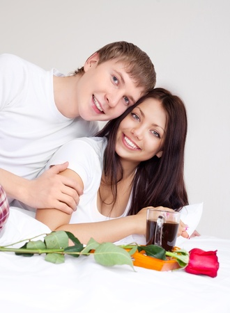 young man bringing his woman a rose and coffee in bed photo