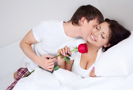 young man kissing his beautiful girlfriend and giving her a rose photo