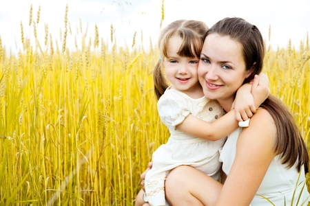 outsides: beautiful young mother and her daughter at the wheat field on a sunny day