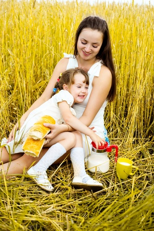 happy mother and her  little daughter having a picnic  in the wheat field   photo