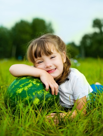 cute little girl with a watermelon on the grass in summertime Stock Photo - 8268271