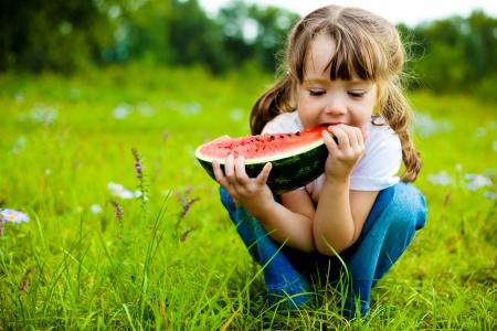 comidas saludables: ni�a bonita, comer sand�a en la hierba durante el verano