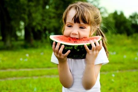 ni�a comiendo: ni�a bonita, comer sand�a en la hierba durante el verano