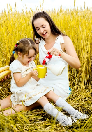 outsides: happy mother and her  little daughter having a picnic  in the wheat field