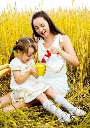 padres hablando con hijos: madre feliz y su peque�a hija tener un picnic en el campo de trigo
