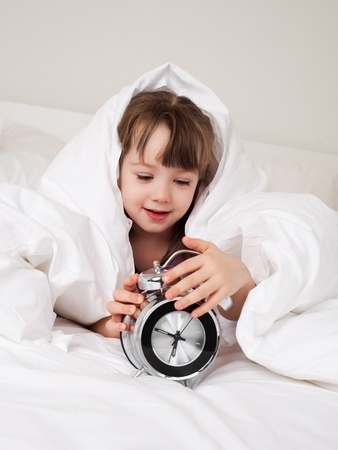 cute little girl waking up in the morning and switching off the alarm clock Stock Photo - 8268179