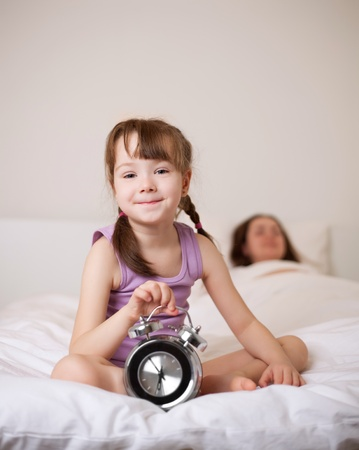 cute little girl waking up in the morning and switching off the alarm clock, her mother sleeping on the background (focus on the child) photo